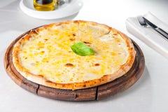 Fromaggi quattro Pizza des Käses vier mit Basilikumblatt auf einem rustikalen hölzernen Brett Stockfotos
