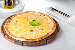 Fromaggi quattro Pizza des Käses vier mit Basilikumblatt auf einem rustikalen hölzernen Brett Stockfoto