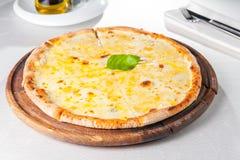 Fromaggi quattro Pizza des Käses vier mit Basilikumblatt auf einem rustikalen hölzernen Brett auf der gedienten Restauranttabelle Stockbild