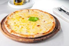 Fromaggi quattro Pizza des Käses vier mit Basilikumblatt auf hölzernem Brett auf der gedienten Restauranttabelle Lizenzfreie Stockbilder