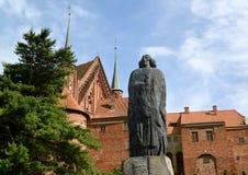 Frombork, Polen Een monument aan de wetenschapper Niicolaus Copernicus tegen de achtergrond van een complexe kathedraal Stock Afbeelding