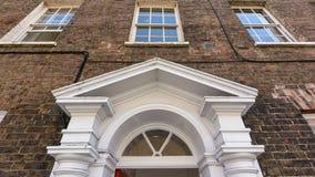 Frontón de la puerta de la madera contra el edificio georgiano del ladrillo rojo imagen de archivo