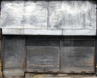 The front of an abandoned store on a street with closed rusting metal shutters over the shop front and door. The front of an abandoned store on a street with stock images