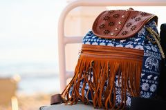 Front View Of Blue Hipster Backpack With White Elephant Pattern And Leather Fringes On Chair By The Beach. A front angle view of a blue hipster backpack with a Stock Images