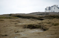 Front beach white house in Brittany, France. White old front beach house in Brittany and rocks in foreground, France Stock Photo