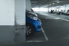 Front of blue car on lot in parking garage. Front of blue car on lot in a parking garage stock images