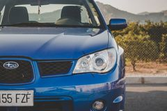 Front a blue Subaru Impreza with mountains in the background. Car`s waiting in the parking lot. Taken on 25 of February 2018. Castellón, Spain Stock Images