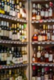 Front of blurred background. Blurred alcohol bottles on shelves in supermarket. Stock Photos