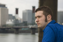 In front of the bridge. Young business man looks out across the river Stock Photography