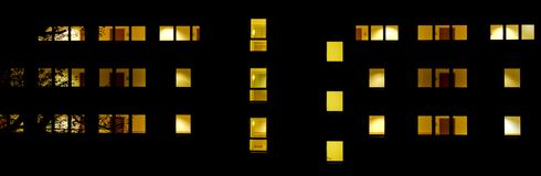 Front of a building with lit-up windows at night Royalty Free Stock Images
