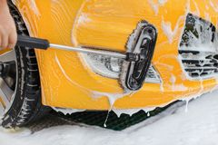 Front bumper and lights of yellow car washed in self serve carwash, brush moving in white shampoo royalty free stock images