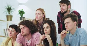 In front of the camera a big group of attractive people friends watching concentrated a movie or a sport match making a. Different emotional faces eating some stock video footage