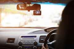 Front camera car recorder, eoman driving a car with video recorder next to a rear view mirror stock image