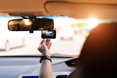Front camera car recorder, woman set video recorder next to a rear view mirror stock image