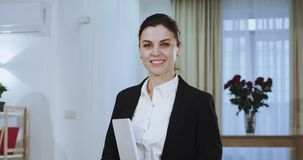 In front of the camera portrait of a attractive businesswoman in a suit smiling large with white teeth and holding a. Tablet in her hand. 4k stock video footage