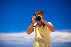 In front of the camera young man with camera in. Hands background the blue sky. This image has attached release Stock Image