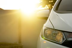 Front of car on evening. Front of white car stop in parking at home with light of sunset on the back side at cement wall. On lamp of car with open light stock photos