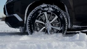 Front car wheel in the deep snow on the winter field detailed Stock Image