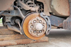 Front car wheel hub, disc, plate, rusted rotor, rusting bearing, in process of damaged tyre replacement. Front old car wheel hub, disc, plate, rusted rotor Royalty Free Stock Photo
