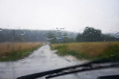 Front car window glass and wipers during heavy rain Stock Photos