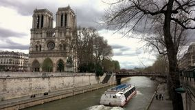 In front of the cathedral Notre Dame de Paris, a excursion boats passes on the seine river. PARIS, FRANCE - APRIL 10, 2018: In front of the cathedral Notre Dame stock footage