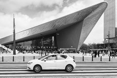 In front of Central Station Rotterdam with a passing white car. Royalty Free Stock Image