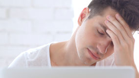 Front Close-Up of Man with Headache Working on Laptop, Pain. High quality Royalty Free Stock Image
