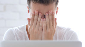 Front Close-Up of Man Upset by Loss, Hiding Face under Hands. High quality Royalty Free Stock Photos