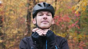 Front close up view of cycling man in black sportswear putting on helmet before training. Young professional triathlete preparing. For cycling training and puts stock video footage