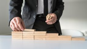 Man behind his office desk constructing steps of wooden pegs. Front closeup view of businessman standing behind his office desk constructing steps of wooden pegs Stock Photos