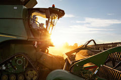 Front of a combine harvester with setting sun. The front part of a combine harvester shown from the side. The sun is setting directly behind casting warm light Royalty Free Stock Image