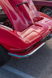 Front Corner of a Red Sports Car. Classic Red Sports Car with the Hood Up.  View angle is the front right corner.  Sky reflections on the hood Royalty Free Stock Image