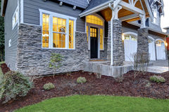 Front covered porch design with stone columns. Front covered porch design boasts stone columns and rock siding that creates immense curb appeal of luxurious home royalty free stock photography