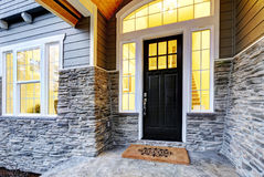 Front covered porch design with stone columns. Front covered porch design boasts stone siding which creates immense curb appeal of luxurious home. Welcome mat stock photos