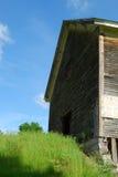 Front der alten hölzernen Scheune, die oben in einen blauen Sommerhimmel erreicht Stockbilder