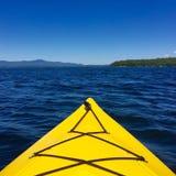 Front des gelben Kajaks auf dem Wasser, das heraus See und Bergen betrachtet Stockfoto