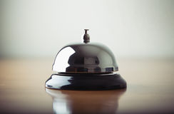 A service bell in a hotel. Front desk service bell on wood base sitting on a wooden desk or counter in a hotel Stock Photos