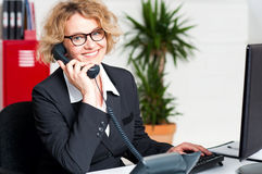 Front desk lady attending clients call Royalty Free Stock Image
