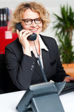 Front desk lady attending clients call Royalty Free Stock Photo