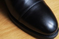 Front detail of a black leather classic shoe on a dance floor Royalty Free Stock Photos