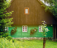 Front detail of traditional mountain chalet, brown and green. Detail of traditional mountain chalet, cottage or hut made of wood surrounded by spruce trees Stock Photo