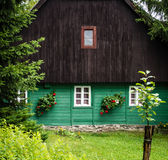 Front detail of traditional mountain cottage, brown and green. Detail of traditional mountain chalet, cottage or hut made of wood surrounded by spruce trees Royalty Free Stock Photo