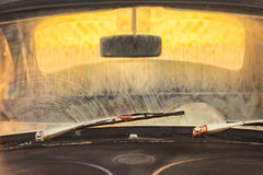 Front of a dirty old car with rusted screen wipers Stock Image