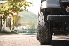 Front of dirty suv and big wheel. Royalty Free Stock Image
