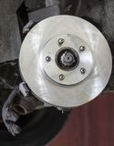 Front disk brake on car in process of damaged tyre replacement. Royalty Free Stock Image