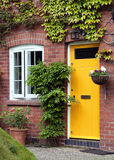 Front door. Yellow front door entrance and old style window of a red brick house or a cottage with hanging flower basket and green ivy Royalty Free Stock Photography