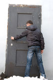In front of the door. Young man is going to open door stock photo