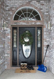 Front Door with Boots and Snow Shovel Royalty Free Stock Photo