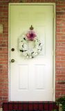 Front door of a brick house. Front door of a red brick house that is decorated with a white rose wreath Royalty Free Stock Images
