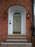 Front door on brick wall. Colonial building with red brick wall and three stairs leading to a white elegant door. Two vintage lights on each side and a wrought Royalty Free Stock Images
